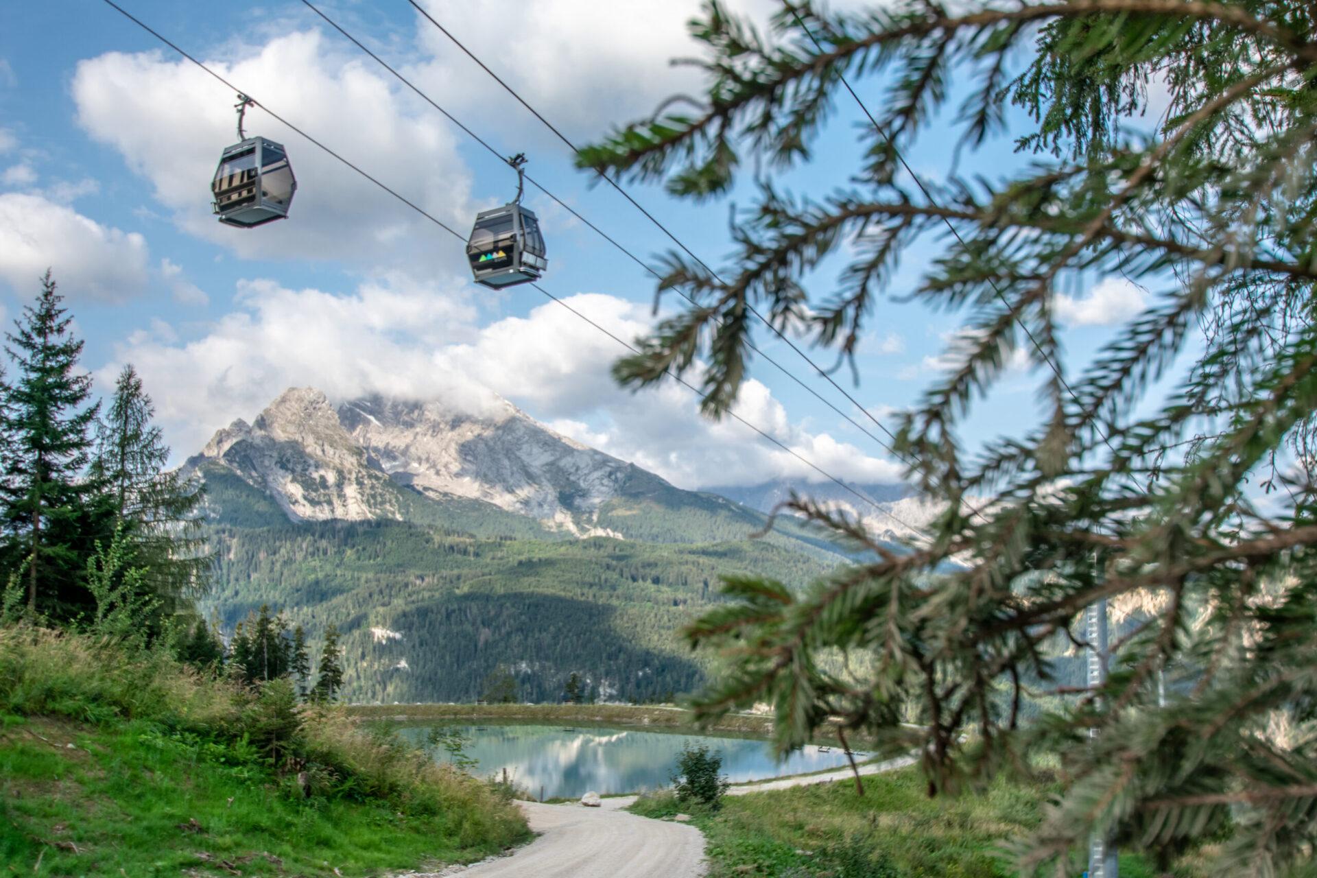 Berchtesgadener Land Tourismus Jennerbahn Gondeln ueber dem Beschneiungsteich scaled e1625564494503